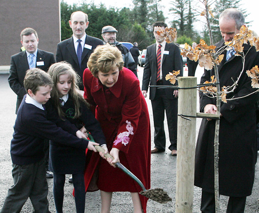 Yacinta McGirr and John McAnespie help to plant a tree with the President